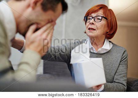 Professional psychologist reassuring suffering man