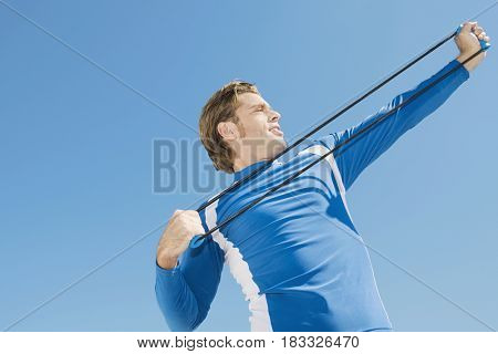 Hispanic man stretching with exercise band