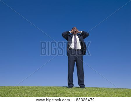 African businessman yelling and covering ears