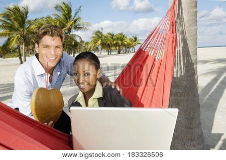 Hispanic couple with laptop and tropical cocktail