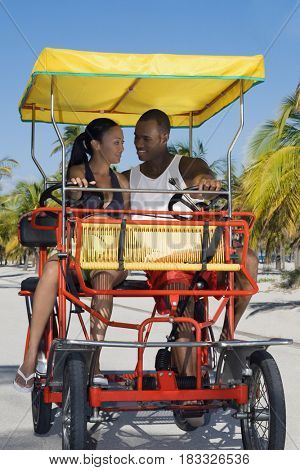 Multi-ethnic couple riding in pedal cart