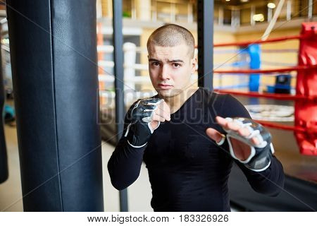 Portrait of determined young muscular man standing in fight pose and looking at camera  during boxing practice in sports club