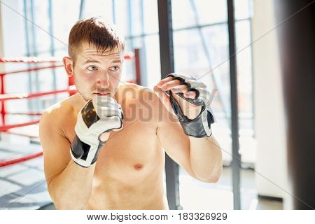 Portrait of sweaty shirtless sports man hitting punching bag during boxing practice in sunlit fight club