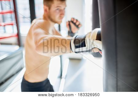 Portrait of shirtless muscular sportsman hitting punching bag during boxing practice in fight club, focus on boxing glove hitting sandbag with strength