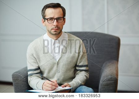 Serious psychiatrist in armchair making notes on paper