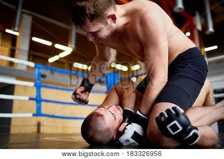Portrait of professional wrestlers fighting in boxing ring: man hitting bloody opponent in face tackling him to floor