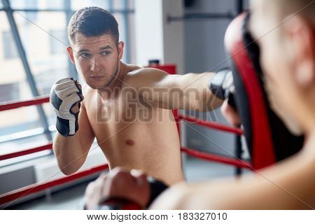 Portrait of handsome shirtless man practicing straight hitting  focus mitts with partner in fighting club