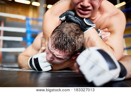 Portrait of shirtless professional wrestlers fighting in boxing ring: tackling opponent to floor and headlocking, suffocating him
