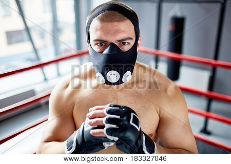 Portrait of shirtless boxer standing in boxing ring looking at camera with determination wearing training mask, ready to fight