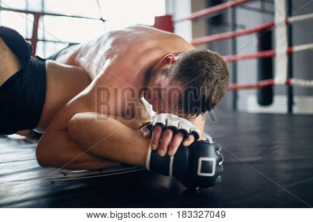 Portrait of shirtless sweaty wrestler fighting in boxing ring: tackling opponent with throw down and locking him