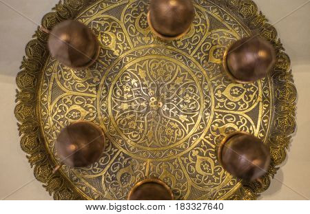Top view of an ornamental golden tray with an intricate arabic design. Close up of tea tray with its details.