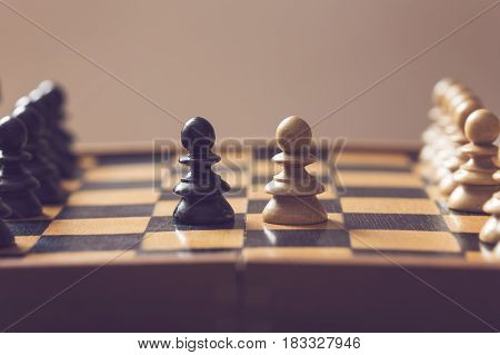 Wooden chess board and pieces black and white pawns positioned against each other. Selective focus