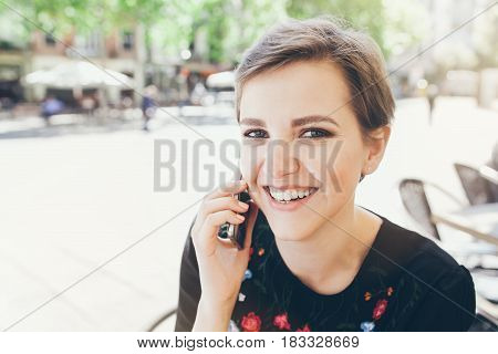 Girl with short pixie haircut is having a phone conversation. People and technology concept. Making phone calls talking to  friends discussing plans for summer.
