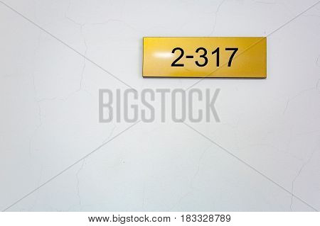 Yellow nameplate with black figures 2-317 hanging on a light wall