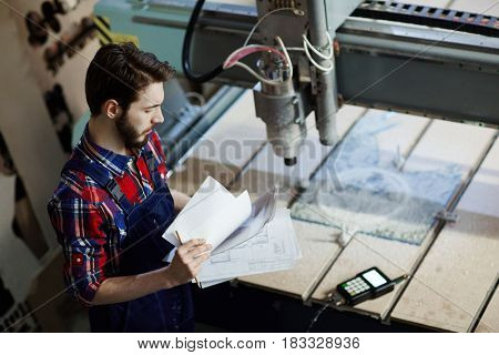 Engineer with papers standing by milling-machine in workshop