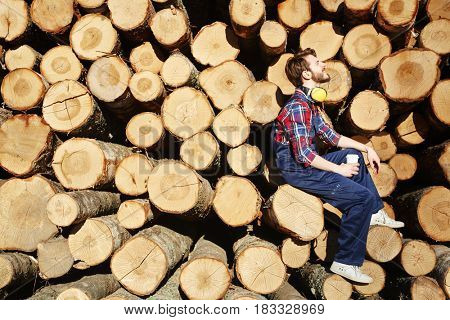Restful lumber sitting on one of logs at coffee-break