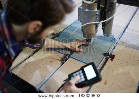 Mechanic fixing glass detail under lathe machine