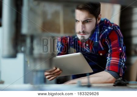 Serious mechanic with touchpad observing work of milling machine