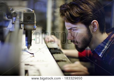 Young mechanic looking at working laser-beam engraving machine in workshop