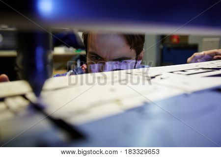 Young engineer looking at laser beam cutting plywood-sheet