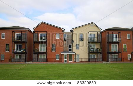 Bracknell, England - April 12, 2017: View of the exterior of a modern apartment block with balconies and a green space in front on a cloudy day in Bracknell, England