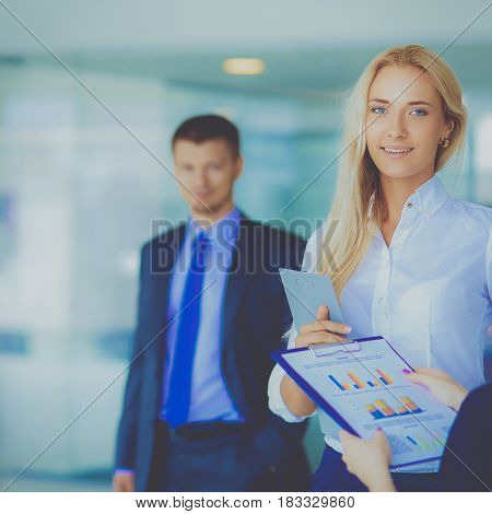 Portrait of young businesswoman in office with colleagues in the background.