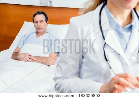 Middle Aged Patient Lying On Bed And Doctor Standing In Front In Hospital