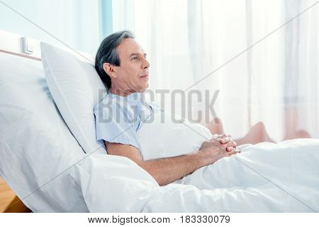 side view of middle aged patient lying in chamber in hospital