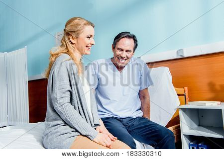 Laughing Wife Visiting Elderly Husband In Hospital
