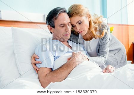 Portrait Of Pensive Wife Visiting Elderly Husband In Hospital