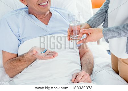 Man Taking Medicines And Woman Holding Glass Of Water Near By