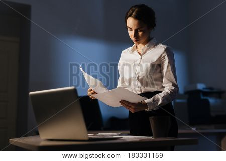 Serious specialist reading business papers by workplace
