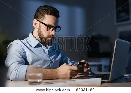 Confident banker with smartphone messaging in office in the evening