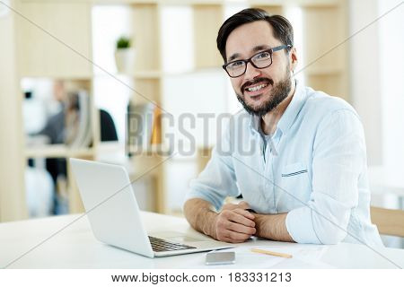 Portrait of Asian adult man smiling and looking at camera while working with laptop in sunlit office