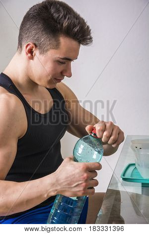 Hungry muscular young man gulping down food glancing across at the camera without pausing as he takes another mouthful