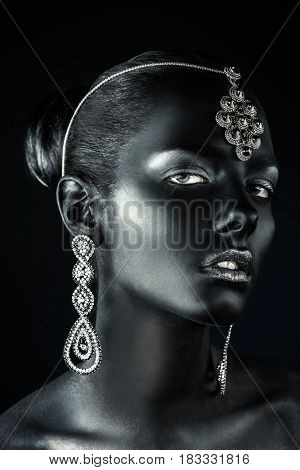 Beauty, fashion portrait. Close-up portrait of a beautiful young woman with black skin, silver glitter lips and beautiful aquamarine jewelry. Body painting project. Make-up and jewelry.