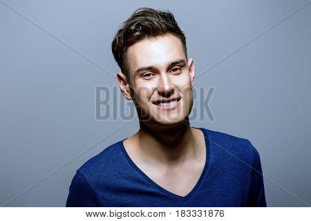 Portrait of a positive smiling young man. Studio shot.