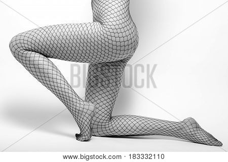slim beautiful female body in tights in white background, monochrome