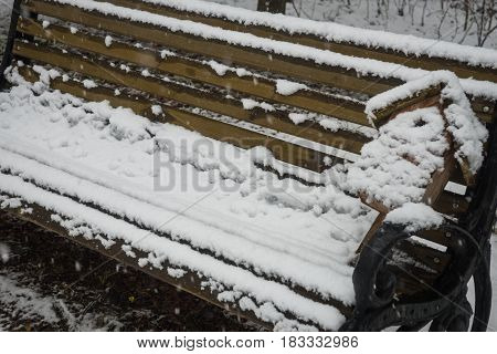 Closeup view of a birdhouse on a bench covered with fresh snow after weather phenomena - snowfall in late April near Moscow