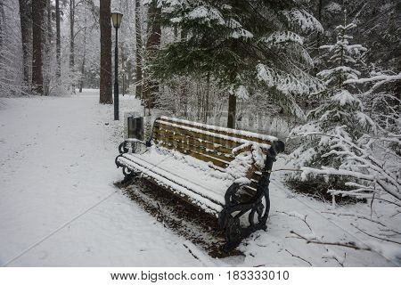 Scenic  view of a birdhouse on a bench covered with fresh snow after weather phenomena - snowfall in late April near Moscow