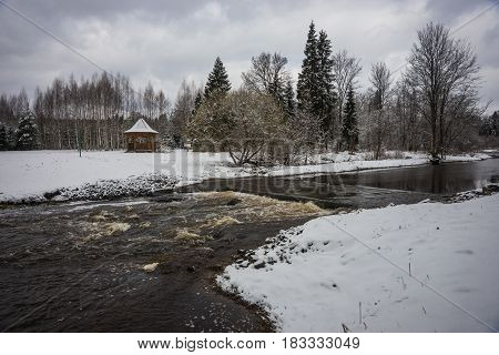 Scenic view of an alcove and a river with its banks covered with fluffy snow during weather phenomena - snowfall in late April near Moscow