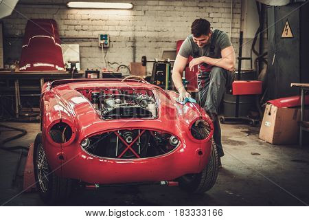 Mechanic polishning car in restoration workshop