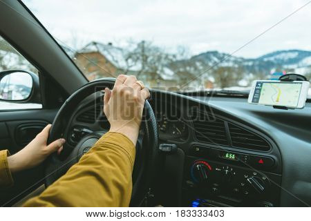 Driver's hands on a steering wheel and blurred road with navigation on mobile phone