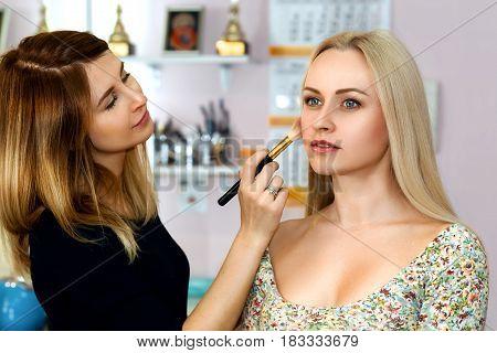 Women make up artist with brush preparing her blonde model