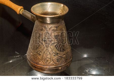Preparing turkish coffee in copper cezve on stove