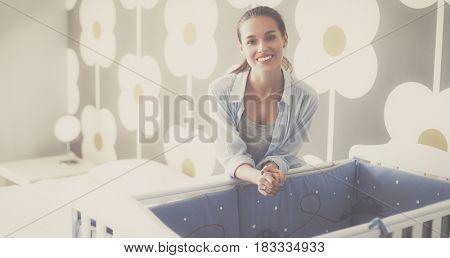 Young beautiful woman standing near children cot