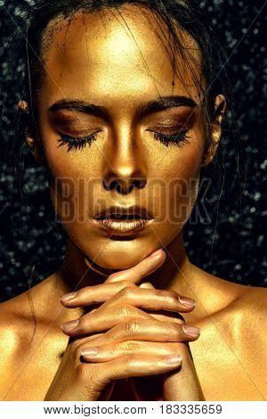 Beauty concept. Close-up portrait of a beautiful young woman with glowing golden skin. Skin care products, cosmetics. Jewellery concept.