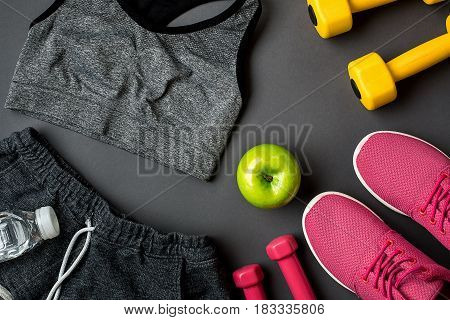 Athlete's set with female clothing, sneakers and bottle of water on gray background. Top view. Copy space. Still life. Ideal for sporty blog.