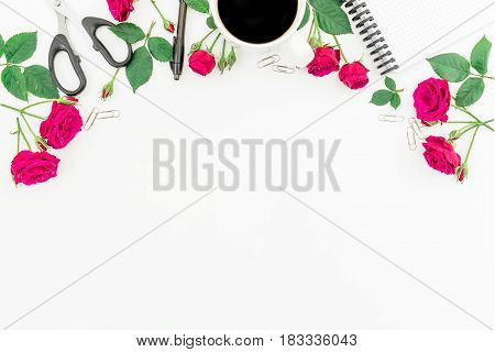 Frame made of red roses, notebook, pen, clips, scissors and black coffee mug on white background. Flat lay, top view. Feminine workspace.