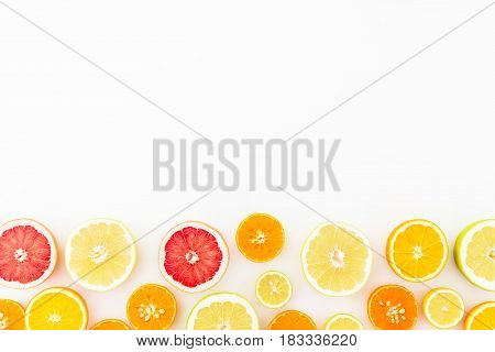 Tropical summer mix with fresh citrus fruits - lemon, orange, mandarin, grapefruit and sweetie on white background. Flat lay, top view.